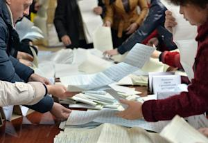 Members of a local electoral commission count ballots…