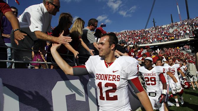 Oklahoma's Landry Jones (12) leads the team as they celebrate with fans following their NCAA college football game against TCU Saturday, Dec. 1, 2012, in Fort Worth, Texas. Oklahoma won 24-17. (AP Photo/Tony Gutierrez)