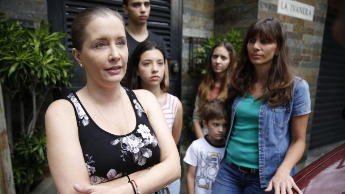 Bony Pertinez, the wife of former Caracas police commissioner Ivan Simonovis, talks to the media while flanked by relatives outside her house in Caracas
