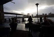 A woman takes photos of the Brooklyn Bridge from South Street Seaport as New Yorkers clean up the morning after Sandy. The hammer blow dealt to New York by superstorm Sandy should raise the alarm for coastal mega-cities in Asia which are more exposed but less equipped to deal with such threats, experts said on Tuesday
