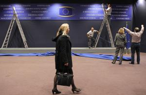Workers adjust a billboard at the European Council…