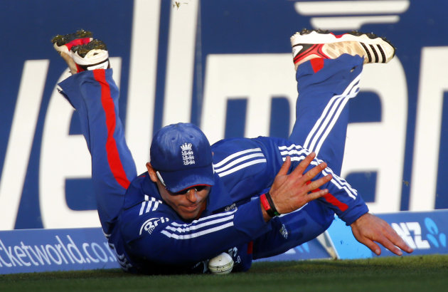 England's Finn slides on the ground to prevent New Zealand from scoring a boundary during their T20 international cricket match in Hamilton
