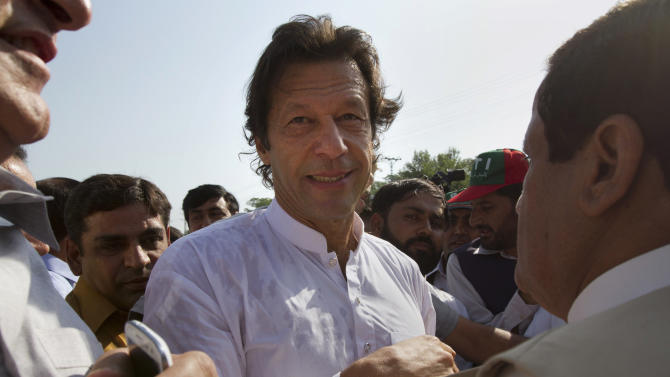 """FILE - In this Saturday, Oct. 6, 2012 file photo, Pakistan's ex-cricket star-turned-politician Imran Khan, center, is surrounded by his supporters as he arrives to lead what organizers are calling the """"peace march,"""" in Islamabad, Pakistan. Khan who founded Pakistan Tehreek-e-Insaf, or the Movement for Justice Party has appealed to a largely young, urban constituency tired with the current crop of politicians and the corruption that plagues the system. Though analysts doubt his party can win enough seats to form the next government his party could affect who comes out on top in the elections. (AP Photo, File)"""