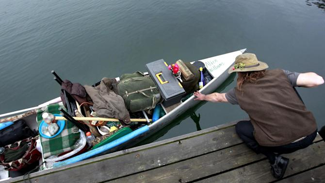 Michael Richard Smith steadies his canoe at a wharf in Boston Harbor, in Boston, Tuesday, Dec. 4, 2012. The 49-year-old Maine native said Tuesday that he's been paddling the waters of metro Boston since at least late summer with all of his possessions aboard a 14-foot, 40-year-old aluminum canoe that he patches with duct tape when necessary. (AP Photo/Steven Senne)