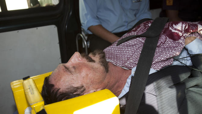 Software company founder John McAfee lies on a gurney inside an ambulance, to be transferred from an immigration detention center to a hospital, in Guatemala City, Thursday, Dec. 6, 2012 . He was examined by a doctor at the detention center, who said that McAfee's heart and blood pressure were normal, but nonetheless was being moved to a hospital after McAfee was found lying on the floor in the room where he was being detained. McAfee who fled Belize was denied political asylum in Guatemala on Thursday and police in Belize said they expected him to be flown back soon for questioning about the killing of a fellow American expatriate.(AP Photo/Moises Castillo)