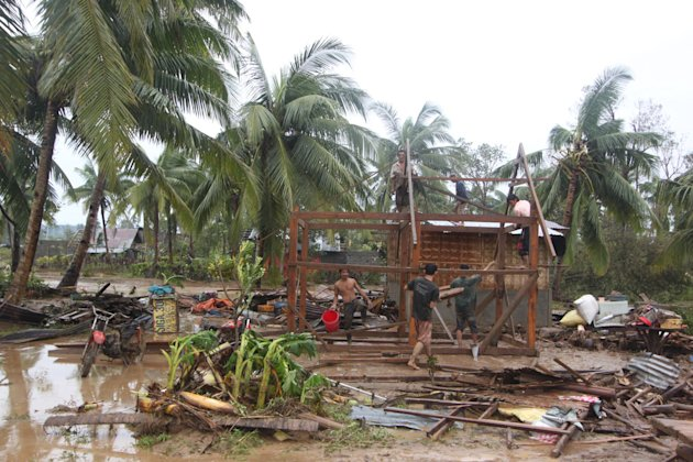 Residents repair their damaged homes after Typhoon Bopha made landfall in Compostela Valley in southeastern Philippines Tuesday Dec. 4, 2012. Typhoon Bopha (local name Pablo), one of the strongest typ