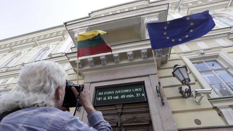 A photographer takes a picture of an electronic billboard, showing the time left before Lithuania joins the Eurozone, over the main entrance of Lithuania's central bank office in Vilnius