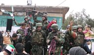 Syrian soldiers who defected join protesters in the al-Khaldiya neighborhood of the restive city of Homs on January 26, 2012. The Britain-based Syrian Observatory for Human Rights said the army launched an offensive on Thursday evening in the Karm al-Zeitoun district of Homs, killing 26 civilians, including nine children, and wounding dozens