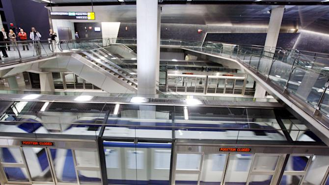 FILE - In this Jan. 25, 2010 file photo, cars from AeroTrain pass behind glass security barriers at Washington Dulles International Airport in Washington. New York City transit officials are considering similar safety barriers between passenger platforms and trains after two people were pushed and a third fell to their deaths on the tracks since early December 2012. (AP Photo/Jose Luis Magana, File)