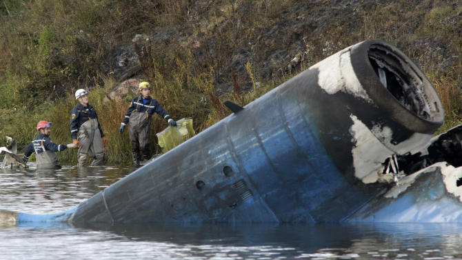 Rescuers work at the crash site of a Russian Yak-42 jet near the city of Yaroslavl, on the Volga River about 150 miles (240 kilometers) northeast of Moscow,  Russia, Wednesday, Sept. 7, 2011. The Yak-42 jet carrying a top ice hockey team crashed while taking off Wednesday in western Russia. The Russian Emergency Situations Ministry said the plane was carrying the Lokomotiv ice hockey team from Yaroslavl.(AP Photo/Misha Japaridze)