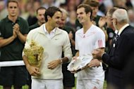 Switzerland's Roger Federer (L) stands with the trophy with runner-up Britain's Andy Murray (R) after his men's singles final victory on day 13 of the 2012 Wimbledon Championships tennis tournament at the All England Tennis Club in Wimbledon, southwest London. Federer won the match 4-6, 7-5, 6-3, 6-4