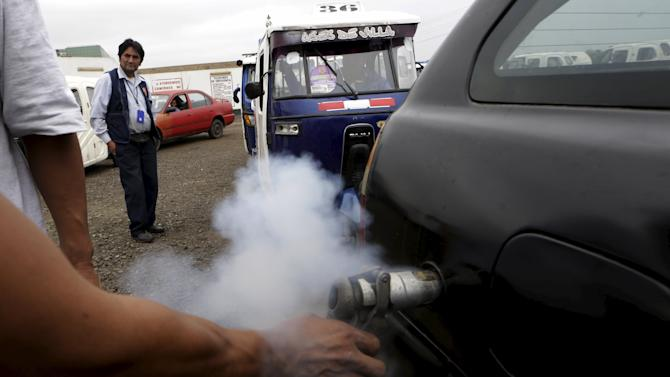 A worker pumps liquefied petroleum gas (LPG) into a vehicle at a service station in Lima
