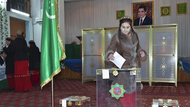 A Turkmenistan woman dressed in traditional clothes casts her ballot at polling station during parliamentary elections in Ashgabat, Turkmenistan, Sunday, Dec. 15, 2013. Voters in the energy-rich Turkmenistan are casting ballots in a parliamentary vote that for the first time features several parties, all of them loyal to the Central Asian nation's autocratic leader. (AP Photo/Alexander Vershinin)