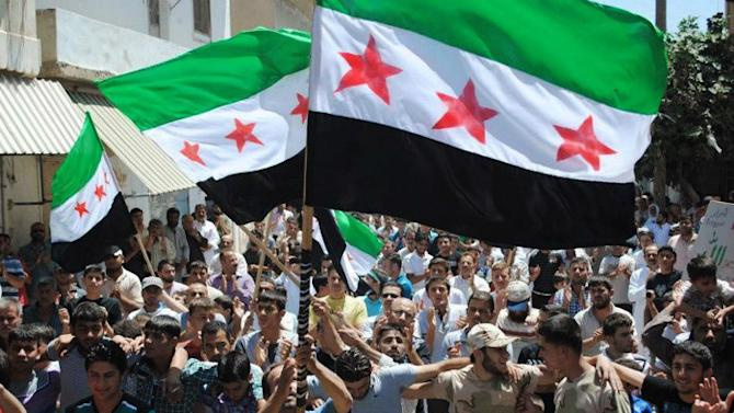 In this citizen journalism image provided by the Local Coordination Committees in Syria and accessed on Friday, June 29, 2012, protesters wave Syrian revolutionary flags and chant slogans during a demonstration in Idlib, north Syria. Syria's main opposition group said nearly 800 people have been killed in violence across the country in the past week which saw some of the bloodiest violence in the 16-month uprising against President Bashar Assad. (AP Photo/Local Coordination Committees in Syria) THE ASSOCIATED PRESS IS UNABLE TO INDEPENDENTLY VERIFY THE AUTHENTICITY, CONTENT, LOCATION OR DATE OF THIS HANDOUT PHOTO