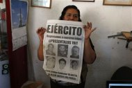 Maria Orozco, mother of Francis Alejandro Garcia Orozco who was abducted along with five other men, shows a poster with their pictures at her shop in Iguala, in the Mexican state of Guerrero February 20, 2013. REUTERS/Tomas Bravo