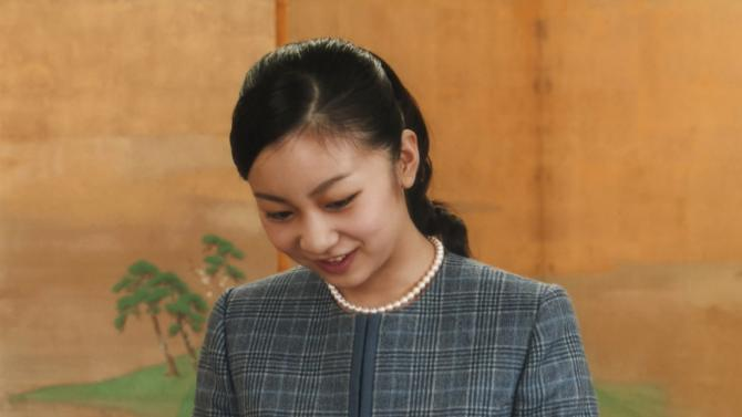 "Handout picture shows Japan's Princess Kako, the second daughter of Prince Akishino and Princess Kiko, looks at an ornament depicting a figure ""Bugaku dancer, Raryoo"" in Tokyo"
