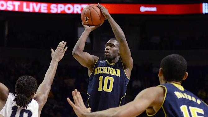 Michigan's Tim Hardaway (10) looks for a shot over Penn State's Brandon Taylor(10) and as Michigan's Jon Horford (15) watches during the second half of an NCAA college basketball game in State College, Pa., Wednesday, Feb. 27, 2013. Penn State won 84-78. (AP Photo/Ralph Wilson)
