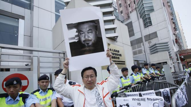 A pro-democracy protester holds a picture of detained Chinese artist Ai Weiwei outside the China Liaison Office in Hong Kong Sunday, April 10, 2011 as they are demanding to release Ai. The sister of the detained Chinese artist says police have still not told the family where he is being held or why, nearly a week after he was grabbed at a Beijing airport.  (AP Photo/Kin Cheung)