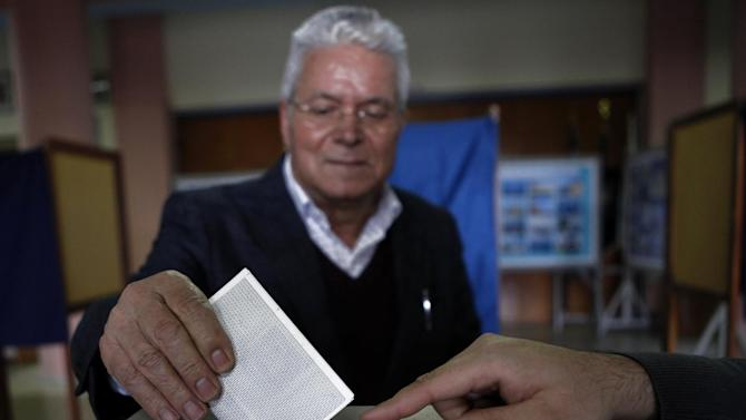 A man votes in the Presidential election in southern port city of Limassol, Cyprus, Sunday, Feb. 17, 2013. Cypriots are voting Sunday for a new president who must tackle a financial crisis that has forced the country to seek international rescue money to stay solvent.  (AP Photo/Petros Karadjias)