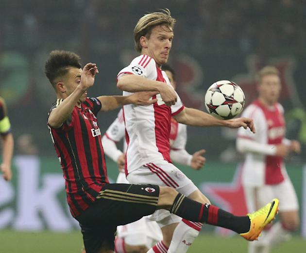 AC Milan forward Stephan El Shaarawy, left, challenges for the ball with Ajax midfielder Christian Poulsen, of Denmark, during a Champions League, Group H, soccer match between AC Milan and Ajax at th
