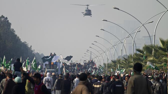 A Pakistani army helicopter monitors supporters of Pakistan Sunni Muslim cleric Tahir-ul-Qadri holding an anti-government rally in Islamabad, Pakistan, Tuesday, Jan. 15, 2013. Thousands of anti-government protesters are rallying in the streets of Pakistani capital for second day despite early-morning clashes with police who fired off shots and tear gas to disperse the crowd. (AP Photo/Anjum Naveed)