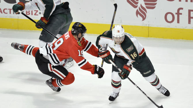Chicago Blackhawks center Jonathan Toews, left, falls as Minnesota Wild left wing Jason Zucker skates with the puck during the first period of an NHL hockey game, Tuesday, March 5, 2013 in Chicago.  (AP Photo/Brian Kersey)