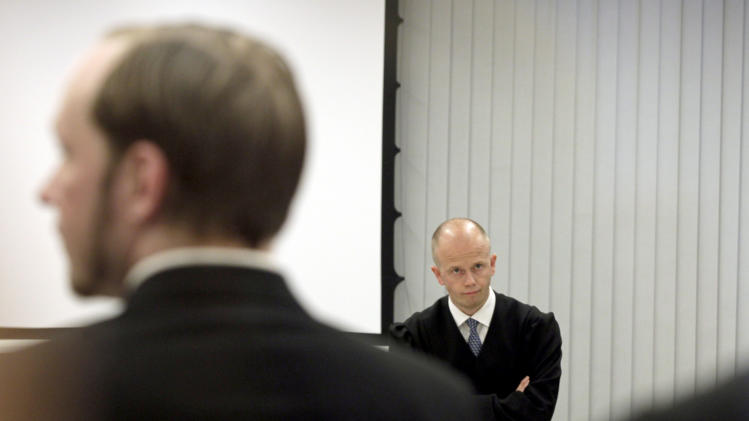 Anders Behring Breivik, the confessed gunman who killed 77 people last year in a bomb and shooting rampage, left, with prosecutor Svein Holden, background, during closing arguments in the court in Oslo, Norway Thursday June 21, 2012. After nearly 10 weeks of grueling testimony of one of the worst peacetime massacres in modern history, it's time for prosecutors to decide their position on whether they think confessed mass killer Anders Behring Breivik is insane or not.   (AP Photo/Berit Roald/Scanpix NTB POOL)
