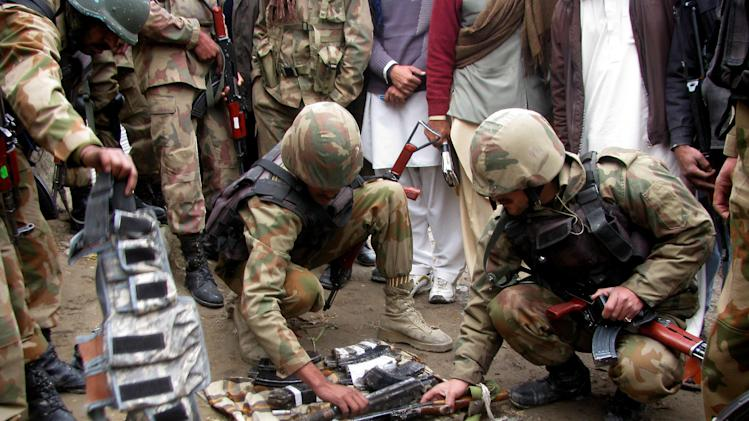 Pakistan army soldiers examine weapons of militants that attacked a police station in Bannu, Pakistan on Thursday, Feb. 14, 2013. Five suicide bombers attacked a police station in the country's northwestern city of Bannu, wounding a police officer. The city's police chief Nisar Tanoli said three of the bombers detonated their explosives vests while the police shot dead the other two. (AP Photo/Ijaz Muhammad)