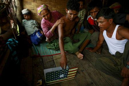 Abdhulami, 22, who was released from a human trafficking boat, points at pictures of people he recognises from the boat as he rests at a refugee camp outside Sittwe