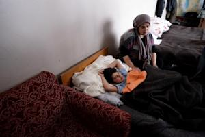 A Syrian refugee woman sits next to her ill son at…