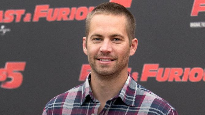 "FILE - In this April 29, 2011 file photo, actor Paul Walker poses during the photo call of the movie ""Fast and Furious 5,"" in Rome. Walker's brothers are filling in to help finish shooting on ""Fast & Furious 7."" Universal Pictures announced Tuesday, April 15, 2014, that Caleb and Cody Walker are filling in for their late brother to complete some remaining filming. Production has resumed on ""Fast & Furious 7"" after it was suspended following Walker's death in late November. (AP Photo/Andrew Medichini, File)"