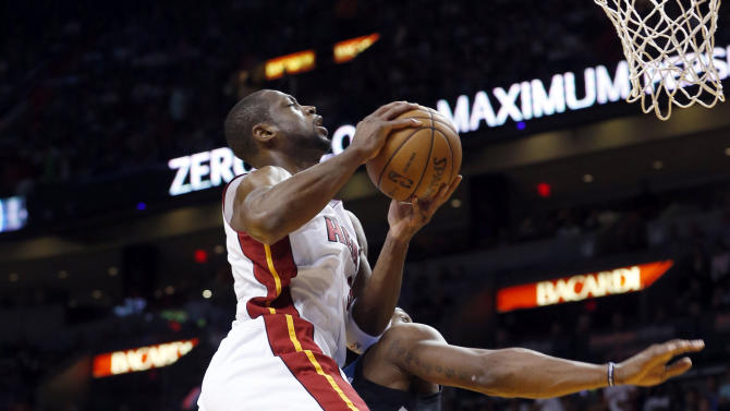Miami Heat's Dwyane Wade, foreground, is fouled by Minnesota Timberwolves' Dante Cunningham as Wade goes to the basket during the half of an NBA basketball game Tuesday, Dec 18, 2012, in Miami. (AP Photo/Alan Diaz)