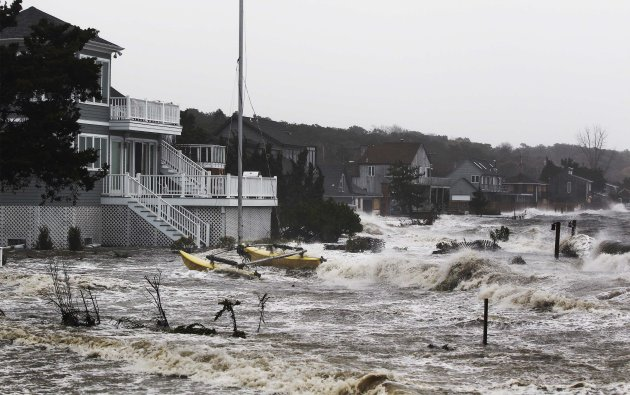 Storm surf kicked up by the high winds from Hurricane Sandy break onto homes in Southampton, New York