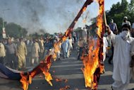 Pakistani Muslim demonstrators burn a US flag as they attempt to reach the US embassy during a protest against an anti-Islam film in Islamabad. Frustrated the US government&#39;s message denouncing an anti-Islam film is failing to be heard, the State Department is turning to social media and television ads to try to stem global protests