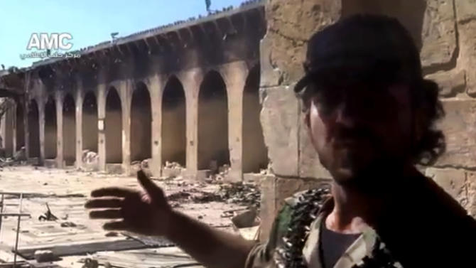 In this image taken from video obtained from Aleppo Media Center AMC, which has been authenticated based on its contents and other AP reporting, shows the damaged famed 12th century Umayyad mosque, background, which was destroyed by shelling, in the northern city of Aleppo, Syria, Wednesday, April 24, 2013. The minaret of a famed 12th century Sunni mosque in the northern Syrian city of Aleppo was destroyed Wednesday, leaving the once-soaring stone tower a pile of rubble and twisted metal scattered in the tiled courtyard. President Bashar Assad's regime and anti-government activists traded blame for the attack against the Umayyad mosque, which occurred in the heart Aleppo's walled Old City, a UNESCO World Heritage site. It was the second time in just over a week that a historic Sunni mosque in Syria has been seriously damaged. (AP Photo/Aleppo Media Center, AMC)