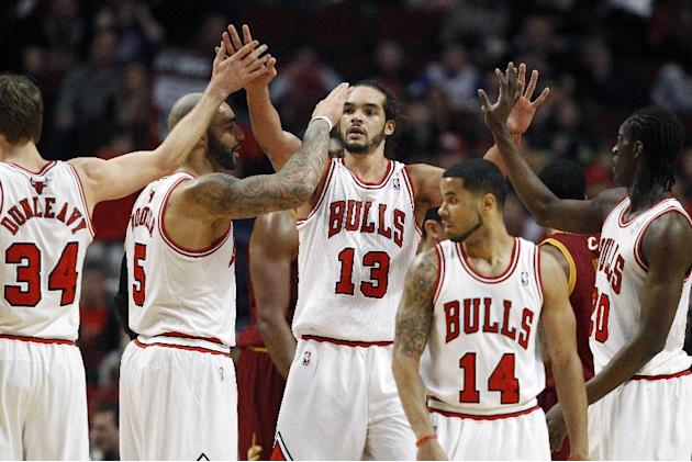Chicago Bulls center Joakim Noah (13) celebrates with teammates after scoring a basket against the Cleveland Cavaliers during the first half of an NBA basketball game on Saturday, Dec. 21, 2013, in Ch