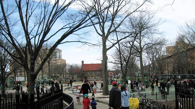 "This April 7, 2013 image shows people in a playground at Washington Park in the Brooklyn borough of New York. A baseball park was located on the site beginning in the 1880s, and the team, later known as the Brooklyn Dodgers, used the Old Stone House, background center, as a clubhouse. A man named Charles Ebbets worked there as a ticket-taker, eventually took over the team, and later built the Dodgers' storied ballpark at Ebbets Field. A new movie, ""42,"" tells the story of Brooklyn Dodger Jackie Robinson, who integrated Major League Baseball and played at Ebbets. (AP Photo/Beth J. Harpaz)"