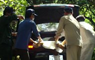 This picture, taken on September 11, shows Cambodian police officials pulling the body of dead local journalist Hang Serei Oudom (C) from a car trunk in Ratanakiri province, some 600 km northeast of Phnom Penh. A military police officer has been arrested in connection with the killing of Oudom who exposed illegal logging activities, according to police