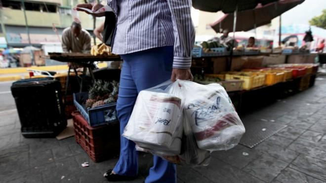 A woman strikes gold at a private store in Caracas, Venezuela, May 15.