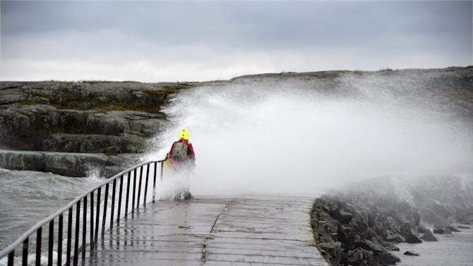A woman is hit by a wave caused by stormy winds in Helsinki