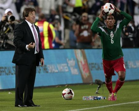 Mexico's coach Miguel Herrera (L) gestures as Juan Carlos Valenzuela throws in the ball during their 2014 World Cup qualifying playoff second leg soccer match against New Zealand at Westpac Stadium in