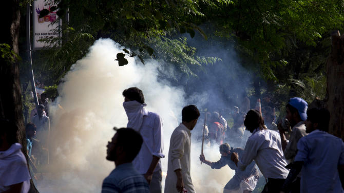 Pakistani protesters trying to push away a tear gas canister police fired to disperse them during a protest in Islamabad, Pakistan on Thursday, Sept. 20, 2012. Hundreds of Pakistanis angry at an anti-Islam film that denigrates the religion's prophet clashed with police in the Pakistani capital Thursday, the most violent show of anger in a day that saw smaller demonstrations in Indonesia, Iran and Afghanistan. (AP Photo/B.K. Bangash)