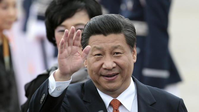 Chinese President Xi Jinping waves upon his arrival at Seoul Military Airport in Seongnam, South Korea. Thursday, July 3, 2014. (AP Photo/Ahn Young-joon).