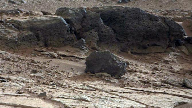 This image provided by NASA shows a rock outcrop in Gale Crater on Mars. The NASA rover Curiosity plans to study the outcrop before heading off to its ultimate science destination, a mountain rising from the middle of the crater, in the next several weeks.(AP Photo/NASA)