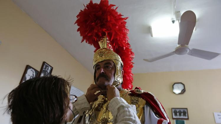 An assistant secures a helmet on a participant dressed as a Roman soldier at the parish centre next to the Rotunda of Mosta, in preparation for a Good Friday procession in Mosta