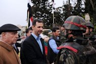President Bashar al-Assad (C) shakes hands with a soldier during his visit to the Baba Amr neighbourhood in Homs on March 27. Syria's regime declared it has defeated those seeking to bring it down while reiterating support for a UN-Arab peace plan, as its troops reportedly shelled rebels in the city of Homs
