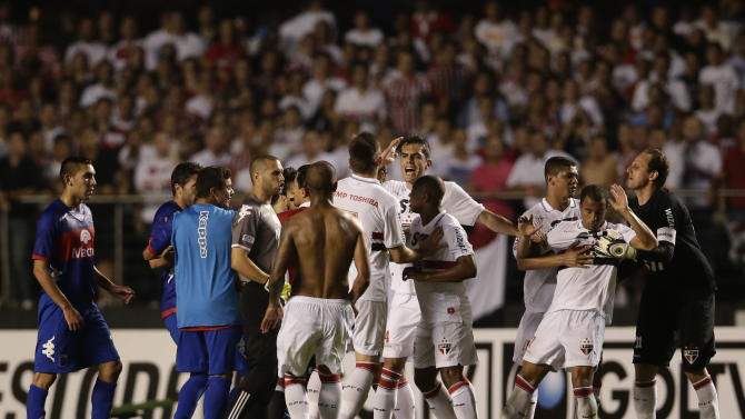 Brazil's Sao Paulo FC's players and Argentina's Tigre's players scuffle at the end of the first half of the Copa Sudamericana final soccer match in Sao Paulo, Brazil, Wednesday, Dec. 12, 2012. (AP Photo/Felipe Dana)