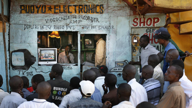 Kenyan men watch television in the Kibera slum of  Nairobi, Kenya Tuesday, March 5, 2013, as preliminary results trickle in for Monday's general election. Kenya on Monday held its first presidential election since the 2007 vote which ushered in months of tribal violence that killed more than 1,000 people and displaced 600,000 from their homes. (AP Photo/Jerome Delay)