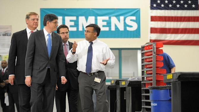 Treasury Secretary Jacob Lew, center left, tours the Siemens manufacturing plant with manager Shujath Ali, right, to view the assembly of electrical drive components for heavy machinery in Alpharetta, Ga., Thursday, March 14, 2013. The drive technology facility makes large traction drive trains for customers including AMTRAK, Caterpillar and the new Atlanta Streetcar initiative. (AP Photo/David Tulis)