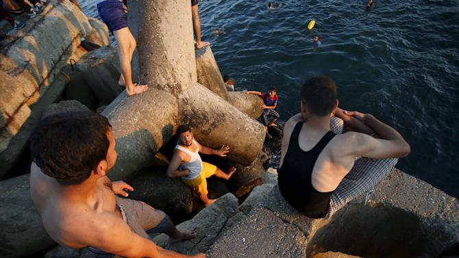 Palestinians wait to jumps into the sea at the seaport of Gaza city